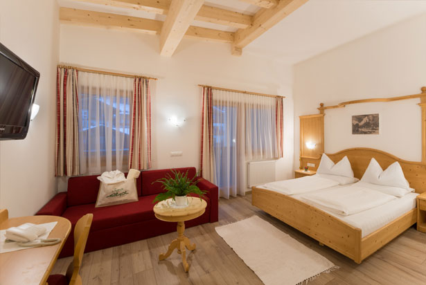 Spacious room with a large balcony facing north towards the Monte Elmo region, lounge area and couch. The comfort rooms Monte Elmo at a quiet position.