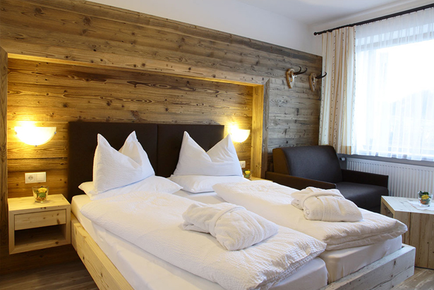 Double room with balcony facing south-east towards the Rotwand (Roda di Vaèl) with a stunning panoramic view of the Sexten / Sesto mountainside.